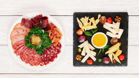 Professional catering. Flat lay of plates with cheese and meat assortment served on white wooden table.