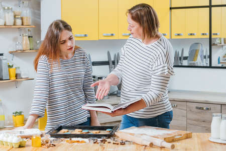 Cooking failure. Mother teaching daughter making biscuits, holding cookery book, pointing out mistake. Zdjęcie Seryjne