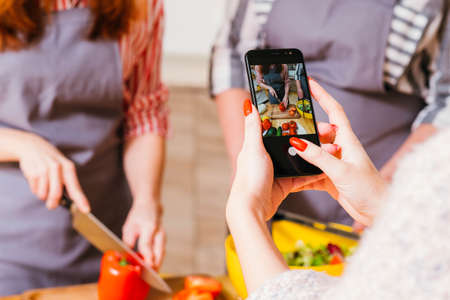 Culinary video blog. Female assistant filming women preparing vegetable salad. Blur background.