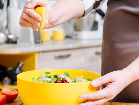 Healthy nutrition. Closeup of female hand squeezing lemon, dressing salad with fresh juice.