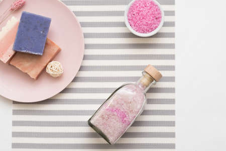 Organic body care cosmetic products. Flat lay arrangement of pink bath salt and handmade soap on striped background. 写真素材