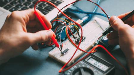 Ingenieur Arbeitsplatz. Techniker testet Mikrocontroller. Draufsicht auf elektronische Komponenten und Drähte.
