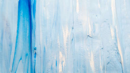 Smeared blue acrylic paint background. Abstract textured layer with white spatters.