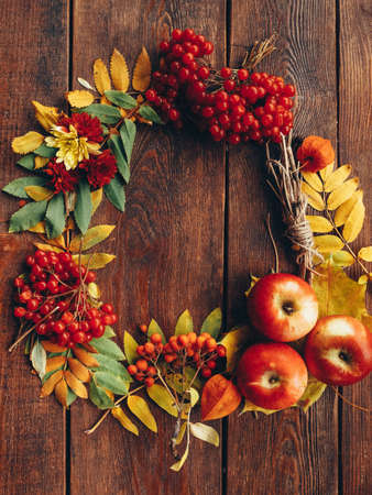 Autumn wrench decor. Colorful fall plants, leaves arranged in round frame on brown wooden background. Copy space. Banco de Imagens