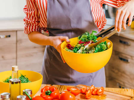 Healthy nutrition. Cropped shot of woman cooking, using kitchen tongs to mix vegetable salad in yellow bowl.