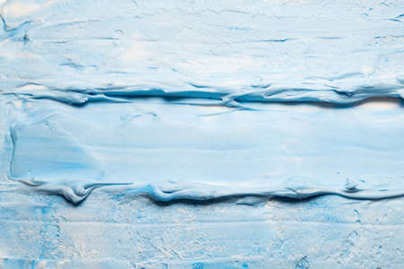 Smeared blue and white acrylic paint background. Tooth paste effect abstract surface.