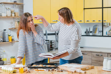 Cooking failure. Mother criticizing daughter for mistake she made in preparing biscuits. Zdjęcie Seryjne