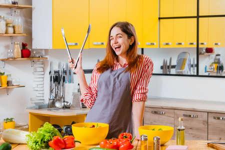 Spaß beim Hausmannskost. Frohe Dame, die mit Küchenzange steht, lächelt, zwinkert und Gemüsesalat zubereitet.
