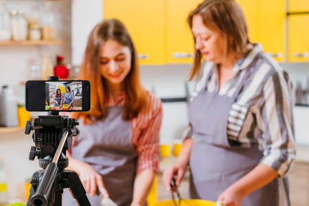 Family culinary video blog. Mother and daughter using smartphone on tripod to film cooking in kitchen. Blur background.
