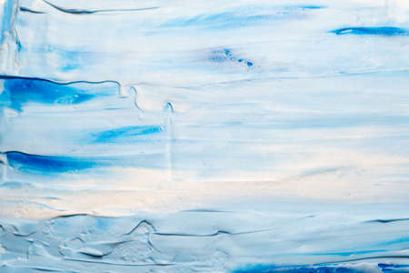 Blue and white acrylic paint. Sky and clouds effect abstract background. Smeared tooth paste art design.