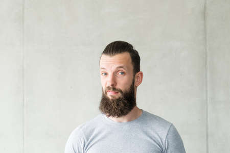 Disgust and dislike. Portrait of bearded hipster guy standing over gray wall background with sceptic facial expression. Copy space. Stock Photo