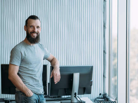 Successful professional career. Cheerful male network engineer standing at his workplace, smiling. Copy space. Stock Photo
