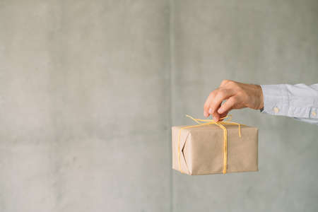 Corporate birthday party. Beige gift box in business man hand. Gray wall background. Copy space.