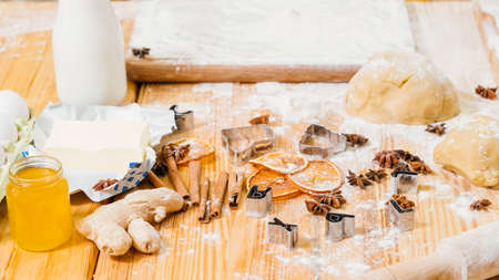 Chef workplace. Creative mess on kitchen table. Ingredients and tools for making gingerbread biscuits.