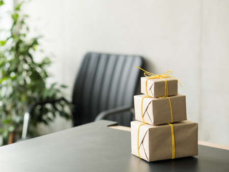 Goods delivery service. Closeup of beige paper wrapped gift boxes stack on office desk. Copy space. Stockfoto