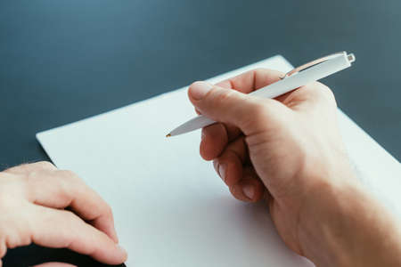 Business correspondence. Closeup of man hand holding pen over blank sheet of paper. Copy space.