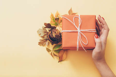 Autumn decoration. Woman hand holding red paper gift box with fall leaves and chestnut. Pastel peach background. Copy space.