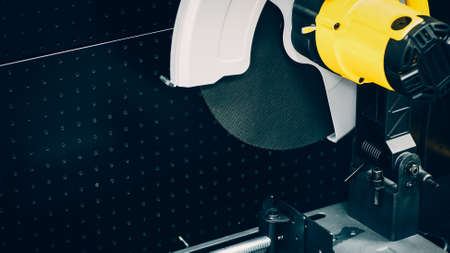 Engineering equipment. Closeup of industrial circular saw over black metal background.