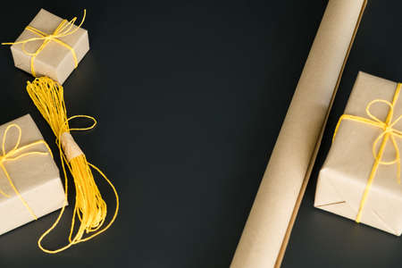 Craft workshop. Flat lay of beige wrapping paper, yellow cord, handmade gift boxes on dark surface. Copy space.