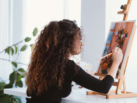 Art hobby. Back view of talented lady with beautiful curly hair working on still life painting at home studio.