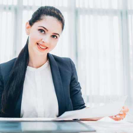 Human resources. Portrait of cheerful female recruiter reviewing resume during interview. Stock Photo