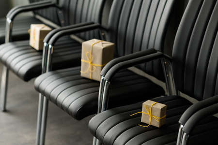 Corporate party celebration. Beige paper gift boxes tied with yellow cord left on black office chairs. Imagens - 126797591