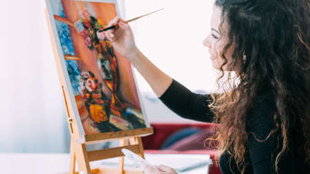Art hobby. Side view of talented lady with beautiful curly hair enjoying working on still life painting at home studio.
