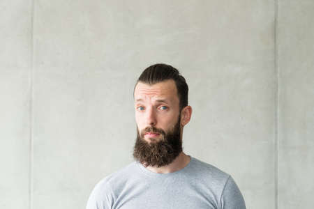 Empathy and compassion. Portrait of bearded hipster guy standing over gray wall background. Copy space.