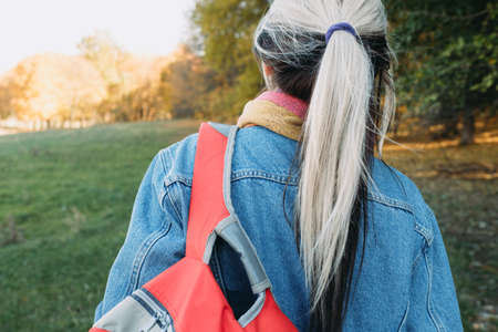 Open air leisure. Back view of lady with backpack in autumn nature park. Blur fall landscape background.