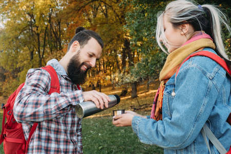 Fall picnic party. Happy couple traveling with backpacks, stopped to drink tea from thermos. Trees and yellow foliage background.