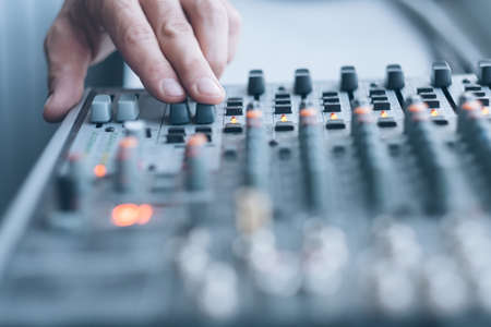 Sound recording studio. Closeup of man hand using professional audio mixer to adjust tune effects.