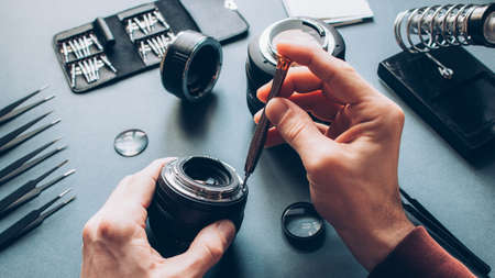 Electronic device service. Top view of man hands repairing photo camera optical dslr lens.