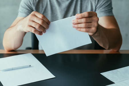 Written communication. Cropped shot of man folding blank mockup letter to send. Copy space. Stock Photo