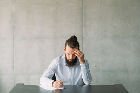 Job application and employment. Pensive bearded man focused on writing test. Gray wall background. Copy space. Stock Photo