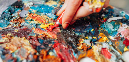 Closeup of colorful palette. Cropped shot of lefthanded female artist mixing acrylic paint. Фото со стока