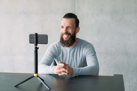 Modern business coaching. Confident hipster guy using smartphone camera to record speech video. Copy space. Stock Photo