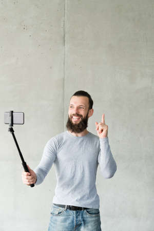 Goods promotion. Cheerful hipster guy using smartphone camera to take selfie, pointing finger up in air. Copy space.