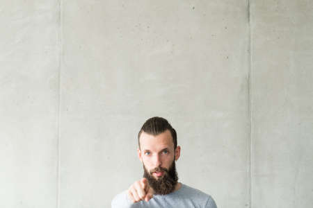 Judge and blame. Portrait of sceptic hipster guy standing over gray wall background, pointing finger at you. Copy space.