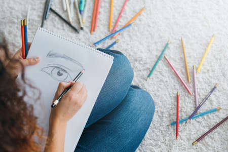 Modern art school. Cropped top view of female student sitting on floor, sketching eye. Colored pencils scattered around. Фото со стока