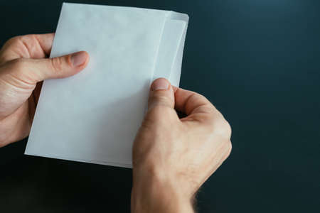 Business correspondence. Closeup top view of man hands holding mockup envelope with letter. Copy space. Stock Photo