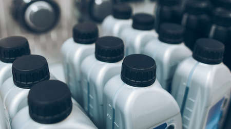 Auto detailing supplies showcase. Closeup of gray plastic bottles with motor oil. Stockfoto