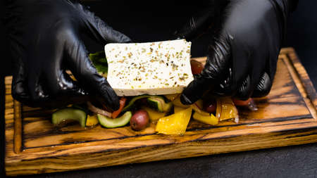 Traditional Greek salad recipe. Chef hands serving feta cheese seasoned with oregano over vegetables on wooden board.
