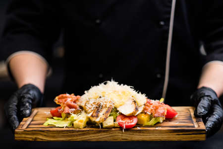 Italian restaurant serving. Chef holding Caesar salad with smoked chicken fillet, bacon chips on wooden board.
