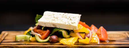 Traditional Greek salad recipe. Fesh vegetables, Kalamata olives and feta cheese seasoned with extra virgin oil.