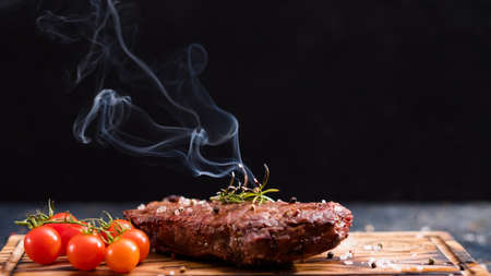 Steakhouse menu. Striploin steak. Grilled beef meat with cherry tomatoes and burning rosemary twig. 写真素材