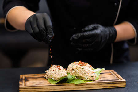 Professional catering. Chef in black cooking gloves seasoning tuna salad on rustic wooden board.
