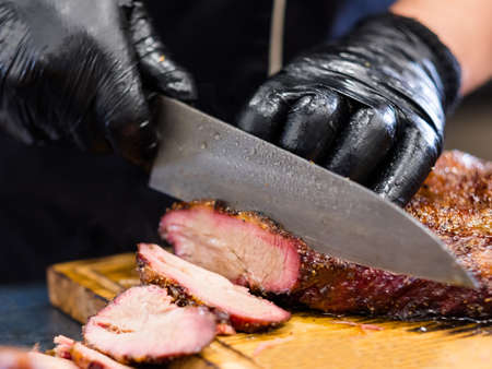 Grill restaurant kitchen. Chef in black cooking gloves using knife to slice smoked beef brisket.