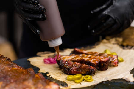 Grill restaurant kitchen. Chef in black cooking gloves pouring sauce over sliced smoked pork ribs.