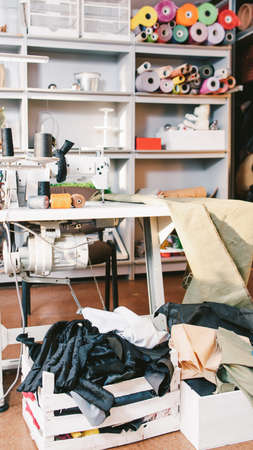 Mess in tailor studio. Seamstress workplace. Sewing machine, cloth rolls, thread spools, clothes in boxes.