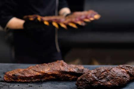 Grill restaurant kitchen. Smoked pork ribs on kitchen table. Blur background.